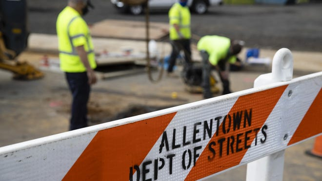 Employees of the Allentown, Pa., streets department work under a street near Jordan Park in Allentown, Pa., Friday, May 29, 2020. Unfilled potholes, uncollected trash, un-mowed grass and, most significantly, fewer police on the street are some of what Allentown says it's contemplating unless Washington helps it plug a multimillion-dollar budget hole left by the coronavirus pandemic. (AP Photo/Matt Rourke)