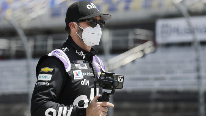 Jimmie Johnson carries a camera as he walks to his car for the start of the NASCAR Cup Series race at Darlington.