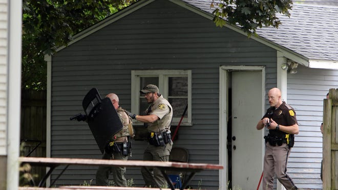 Law enforcement officers serve a search warrant near the corner of 15th and Myrtle streets, following a night of violence in Davenport, that left one officer shot in an ambush style shooting and two other people killed after rioting Monday in Davenport.
