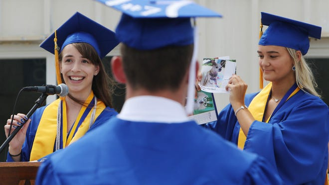 Rachel Johs, left, one of three class valedictorians gives her class address with the help of fellow valedictorian Taylor Ackerman, holding a daily calendar, during the 2020 Notre Dame High School graduation ceremony Sunday held at the school's track in Burlington.