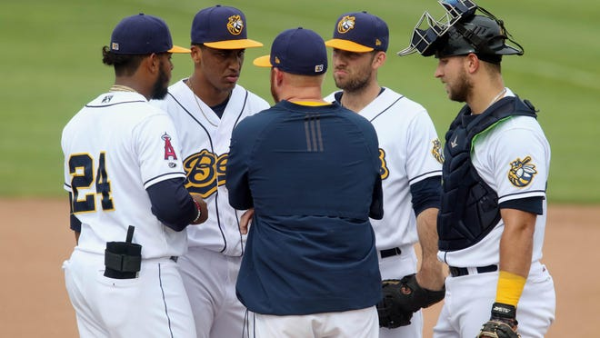 Burlington Bees players are joined on the mound by a coach during the first game of their double header against the Cedar Rapids Kernels, Wednesday May 29, 2019 at Community Field.