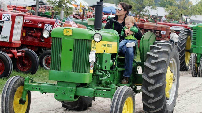 Deb Klopfenstin, holds on to her son, Brooks, while driving her 1959 John Deere tractor to take part in the Cavalcade of Power Parade during 2019 Midwest Old Threshers Reunion in Mount Pleasant. This year's event has been canceled.