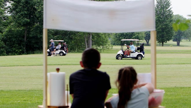 Claire Cameron, 8 and her brother Avery, 10, keep an eye on the golf course as they operate their Summertime Squeezes lemonade stand June 3 from their cousin's home next to the 11th hole of the Flint Hills Municipal Golf Course.
