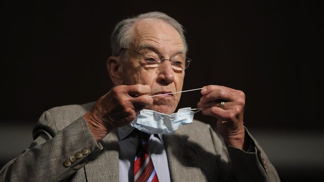 Sen. Chuck Grassley, R-Iowa, puts on a face mask during a Senate Judiciary Committee June 11 on Capitol Hill in Washington.