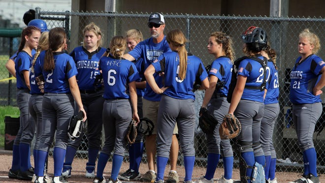 Fort Madison's HolyTrinity Catholic High School's head coach Loren Menke talks with players during their game against West Burlington-Notre Dame June 30 at West Burlington's Barb Carter Field.