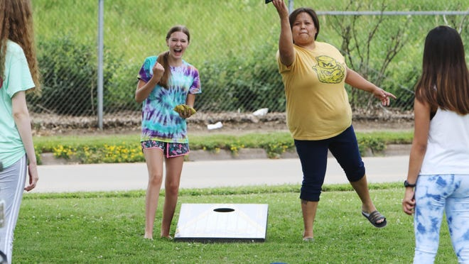 Kaeley Hunerdosse, reacts to her toss as Michelle Navarra tosses a bag during a game of corn hole at Rafiekha Navayra's 15th birthday celebration Friday in West Burlington. Rafiekha and her friends who had a sleepover the night before were playing the game before continuing the celebration at FunCity.
