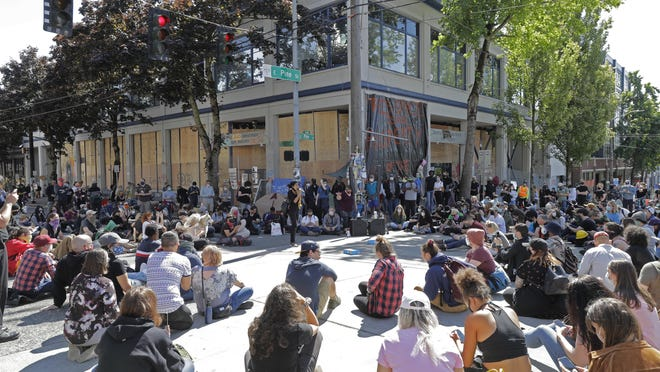 """Protesters listen to a speaker Thursday as they sit in front of the Seattle Police Department East Precinct building, which has been boarded up and abandoned except for a few officers inside, inside what is being called the """"Capitol Hill Autonomous Zone"""" in Seattle."""