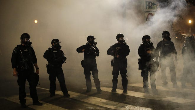 Federal officers are surrounded by smoke as they push back demonstrators during a Black Lives Matter protest at the Mark O. Hatfield United States Courthouse Wednesday, July 29, 2020, in Portland.