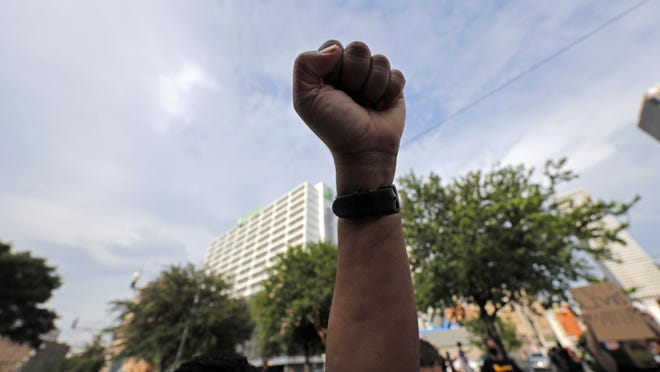A demonstrator raises a fist in the air during a peaceful march Tuesday in downtown New Orleans over the death of George Floyd, a black man who died after being restrained by Minneapolis police officers on Memorial Day.