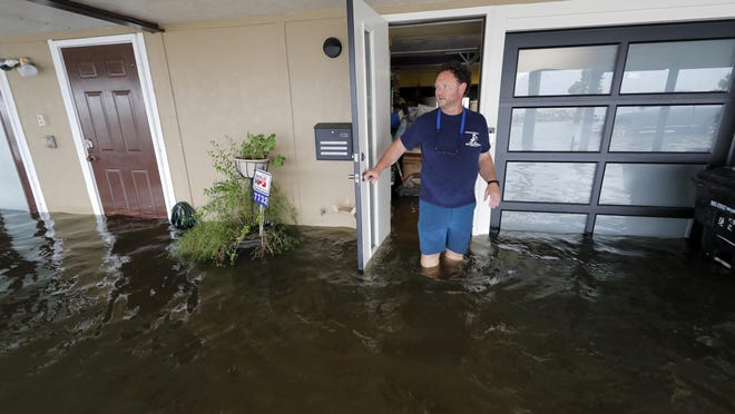 Rudy Horvath walks out of his home, a boathouse in the West End section of New Orleans, on Sunday as it takes on water a from storm surge in Lake Pontchartrain in advance of Tropical Storm Cristobal.