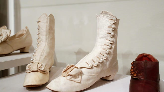 """Antique boots from the 1870s on display at the """"Walk This Way: Historic Footwear from the Stuart Weitzman Collection"""" exhibition."""