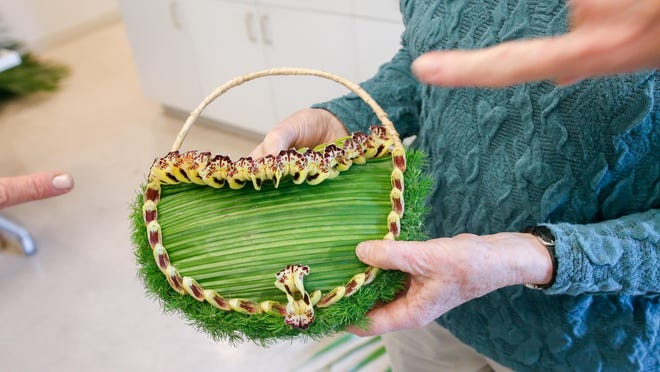 Made of leaves, moss and orchid petals, Francoise Weeks created a functional purse for her workshop Thursday at The Society of the Four Arts.