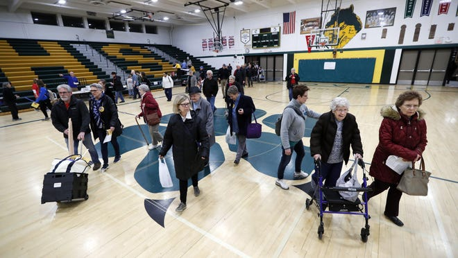Local residents enter an Iowa Democratic caucus at Hoover High School, Monday, Feb. 3, 2020, in Des Moines, Iowa.