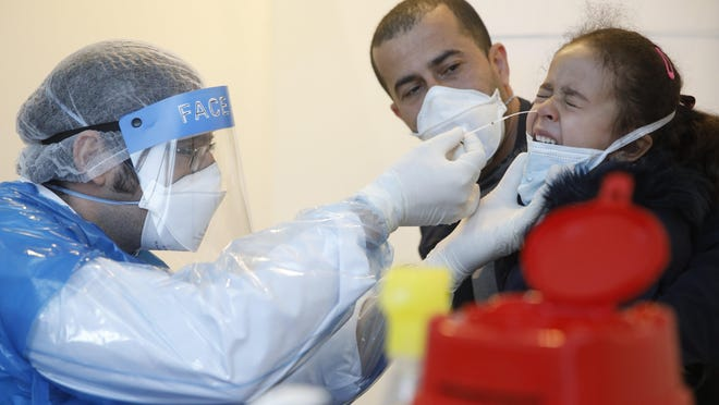 A health-care worker collects a swab sample to be tested with the Coronavirus from a young girl at the European Parliament in Strasbourg, eastern France, Tuesday, May 12, 2020. The European Parliament's headquarters in Strasbourg is temporarily used a coronavirus testing center.