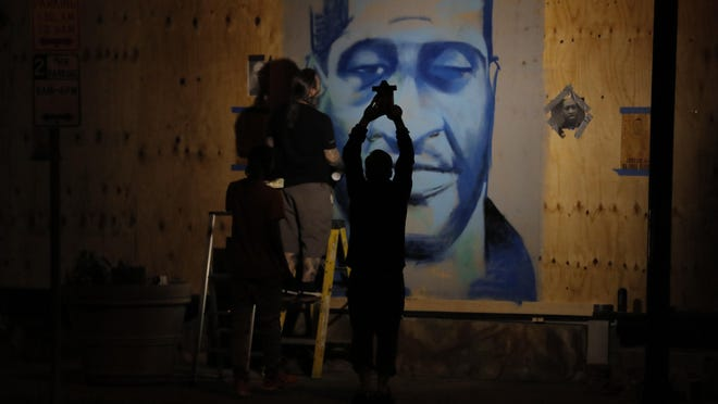 An artist creates an image of George Floyd Thursday, May 28, 2020, in Minneapolis. Violent protests over the death of Floyd, the black man who died in police custody broke out in Minneapolis for a third straight night.
