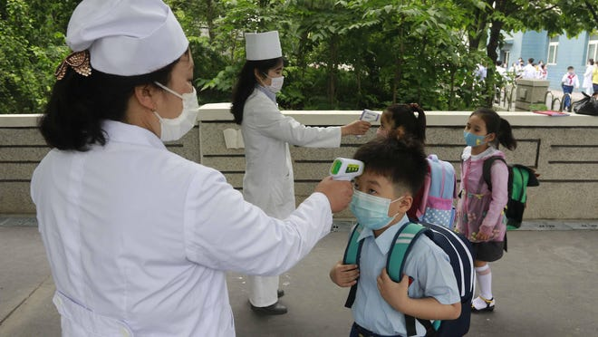 Kim Song Ju Primary school students have their temperatures checked before entering the school in Pyongyang, North Korea, Wednesday, June 3, 2020. All the schools in the country start their lessons this month after delays over concern about the new coronavirus.