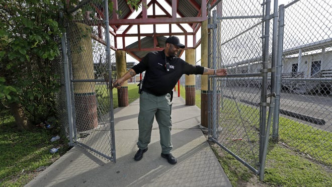 A school resource officer locks the gates of an elementary school.