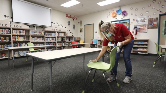 Wearing a mask and face guard as protection against the spread of COVID-19, a custodian wipes down a chair in the library of an elementary school.