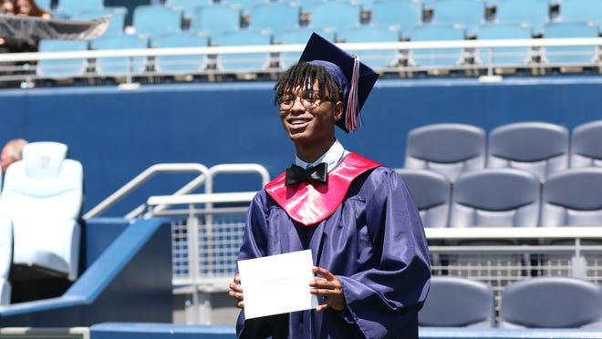 Truman High School graduate Julian Clardy strikes a pose after receiving his diploma folder during Saturday's commencement ceremony at Children's Mercy Park in Kansas City, Kansas