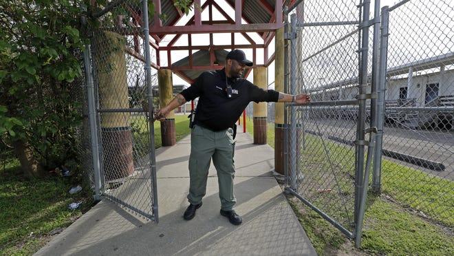 A school resource officer locks the gates of an elementary school.