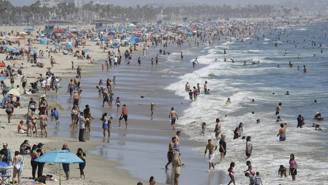 Visitors crowd the beach Sunday, July 12, 2020, in Santa Monica, Calif., amid the coronavirus pandemic. A heat wave has brought crowds to California's beaches as the state grappled with a spike in coronavirus infections and hospitalizations.