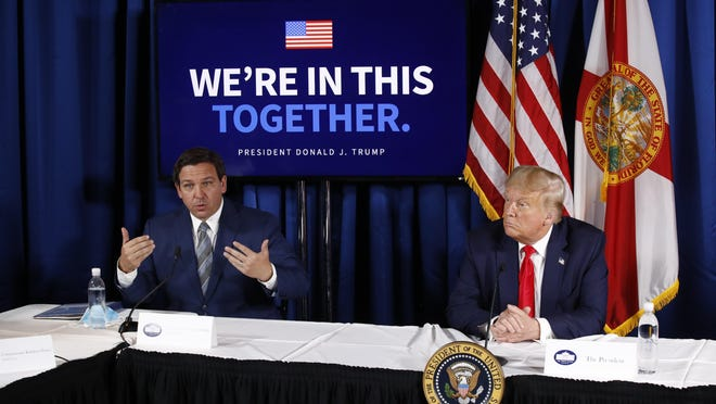President Donald Trump listens as Florida Gov. Ron DeSantis speaks during a roundtable discussion Friday on the coronavirus outbreak and storm preparedness at the Pelican Golf Club in Belleair.