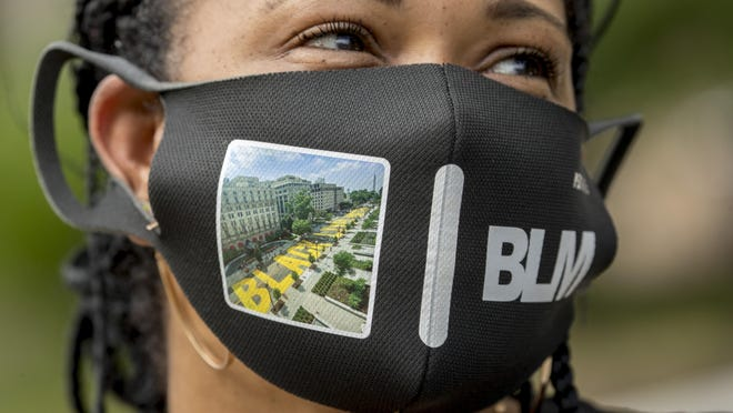 Shawna Jacobs of Fort Washington, Md., wears a mask with a photograph of 16th Street Northwest renamed Black Lives Matter Plaza near the White House, on June 19 in Washington.
