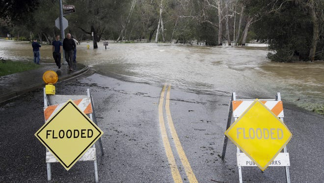 Signs block a road which runs into the overflowing Coyote Creek Feb. 21, 2017, in Morgan Hill.