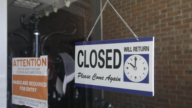 A closed sign is posted on the window of a barbershop Saturday in Burbank. Gov. Gavin Newsom said Monday that salons and barbershops can reopen if they provide their services outside.