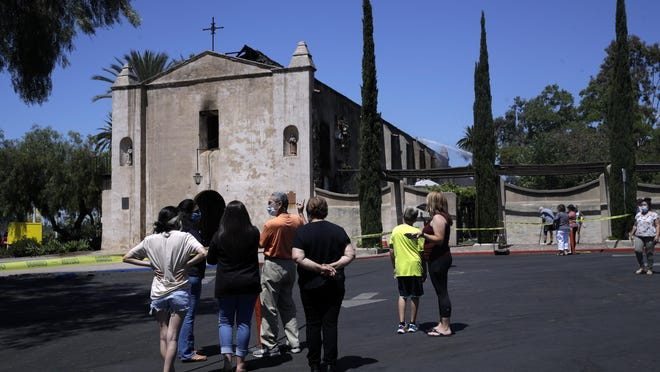 Curious onlookers stand outside the San Gabriel Mission in the aftermath of a morning fire Saturday, July 11, 2020, in San Gabriel, Calif. The fire destroyed the rooftop and most of the interior of the nearly 250-year-old California church that was undergoing renovation.