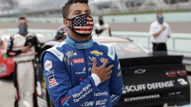 "Bubba Wallace stands for the national anthem before a recent race in Florida. On Sunday, a noose was discovered in his garage stall at Talladega, but Wallace said ""this will not break me, I will not give in nor will I back down."""