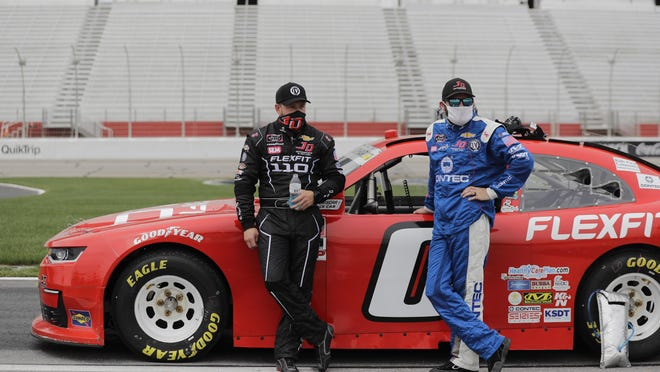 Jeffrey Earnhardt, left, stands by his car before a NASCAR Xfinity Series auto race at Atlanta Motor Speedway, Saturday, June 6, 2020, in Hampton, Ga.