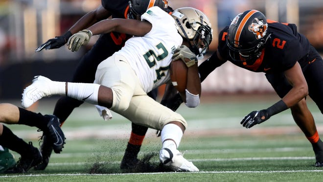 Massillon's Xavier Andrews (33) closes in on St Vincent St Mary's Josh Nickerson during last season's opener. Andrews, Zach Catrone, Terrence Rankl and Andrew Wilson-Lamp were chosen as team captains for the Tigers this season.