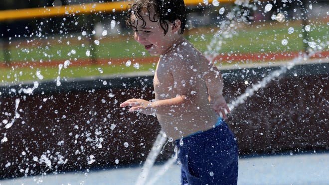 Zackary Khouzam, 2, of Englewood, enjoys the water at Veterans Field Park, in Edgewater. The park thermometer read 100 degrees. Sunday, July 26, 2020