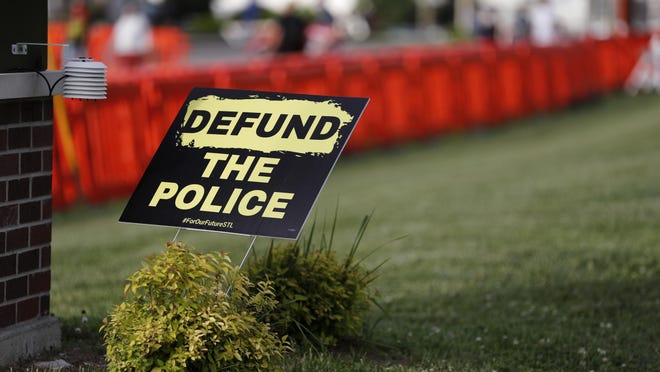 A sign advocating for defunding the police is seen outside the police station in Florissant, Mo.