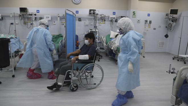 Dr. Jose Veren, who is infected with the new coronavirus, exercises his legs while sitting in a wheelchair in an intensive care unit designated for COVID-19 patients at the Alberto Sabogal Hospital in Lima, Peru, Monday, July 27, 2020. The 37-year-old doctor who specializes in family medicine says he feels reborn after recovering consciousness from a prolonged coma due to the virus.