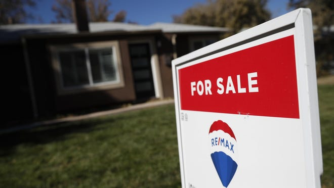 FILE - In this Oct. 22, 2019, file photo, a sign stands outside a home for sale in southeast Denver. On Friday, Feb. 21, 2020, the National Association of Realtors reports on sales of existing homes in January,