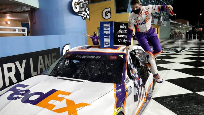 Denny Hamlin jumps from his car after winning a NASCAR Cup Series auto race Sunday, June 14, 2020, in Homestead, Fla.