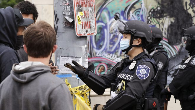 A police officer talks with a protester on Wednesday in Seattle, where streets had been blocked off in an area demonstrators had occupied for weeks.