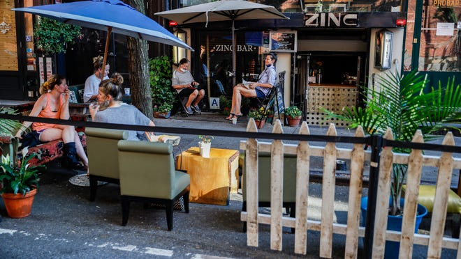 Customers dine outside PhoBar in June in New York. New York City Mayor Bill de Blasio says he is delaying the planned resumption of indoor dining at restaurants in the city out of fear it would ignite a a spike in coronavirus infections.