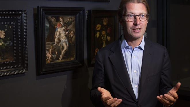 "Rijksmuseum director Taco Dibbits, standing in front of Bartholomeus Spanger's ""Body of Christ Supported by Angels"" oil on copper painting, left, discusses the gift of the major painting the cultural institution received to underscore support for the victims of the coronavirus pandemic and the crisis that museums face world wide, which went on display in Amsterdam, Netherlands, Monday, June 1, 2020. The Dutch government took a major step to relax the coronavirus lockdown, with bars, restaurants, cinemas and museums reopening under strict conditions."