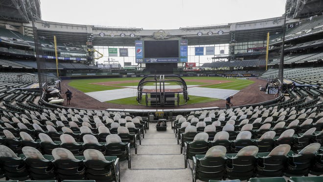 Fan cutouts sit in seats behind home plate Friday at Miller Park after it was announced that the baseball game between the Milwaukee Brewers and Cardinals in Milwaukee, was postponed after two Cardinals employees tested positive for the coronavirus.