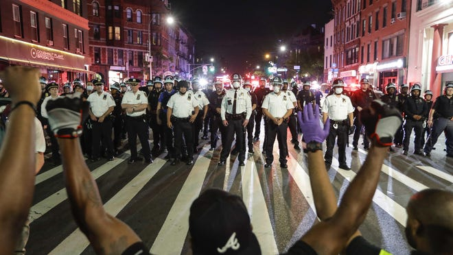 Protesters take a knee on Flatbush Avenue in front of New York Police Officers during a solidarity rally for George Floyd, Thursday, June 4 in the Brooklyn borough of New York.