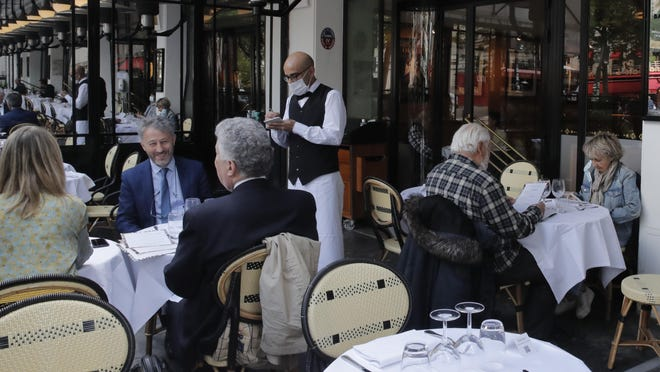 A waiter takes the order at La Coupole restaurant, Monday, June 15, 2020 in Paris.