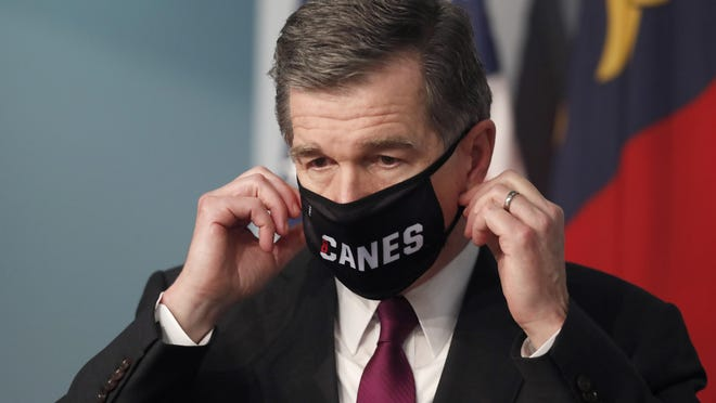 Gov. Roy Cooper on Wednesday prepares to take off his Canes mask before speaking during a briefing at the Emergency Operations Center in Raleigh.