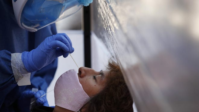 Dr. Diana Pacheco collects a nasal swab for a COVID-19 test, in a mobile diagnostic tent in the Xochimilco district of Mexico City on Wednesday, July 22.