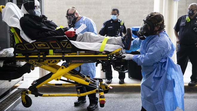 Paramedics load a person who has been staying overnight at Philadelphia International Airport into an ambulance in Philadelphia, Tuesday, May 26, 2020. Officials on Tuesday began removing dozens of people who have been sleeping at the city's airport during the coronavirus pandemic.
