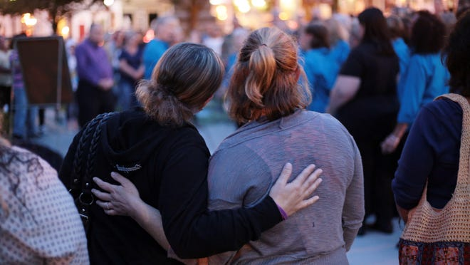 Two women console each other during a vigil in honor of International Overdose Awareness Day in Newton Thursday, August 31, 2017. The annual event is set for Monday night on the Newton Green.
