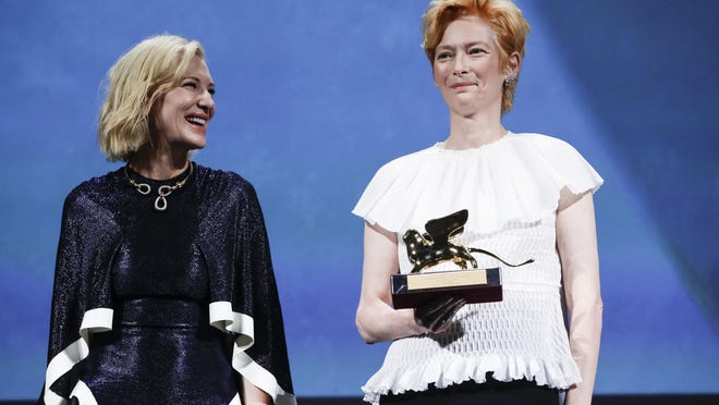 Actress Tilda Swinton, right, holds the Golden Lion for Lifetime Achievement, which was presented by Jury President Cate Blanchett during the opening ceremony of the 77th edition of the Venice Film Festival in Venice, Italy.