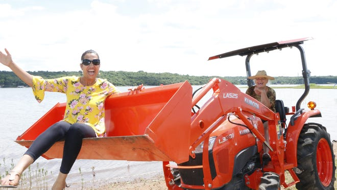 Riti Chikkerur gets a lift in the bucket of a tractor operated by Fran McDuff on the shores of North Lake Brownwood.